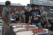 AUGUST 24, 2018  ATHENS, OHIO:<br /> New Freshman students walk through a line and pick up slices of pizza and an assortment of other dinner foods as they took a seat on the football field in Peden Stadium before watching Avengers Infinity Wars after posing for the first year class photo on August 24, 2018 in Athens, Ohio.