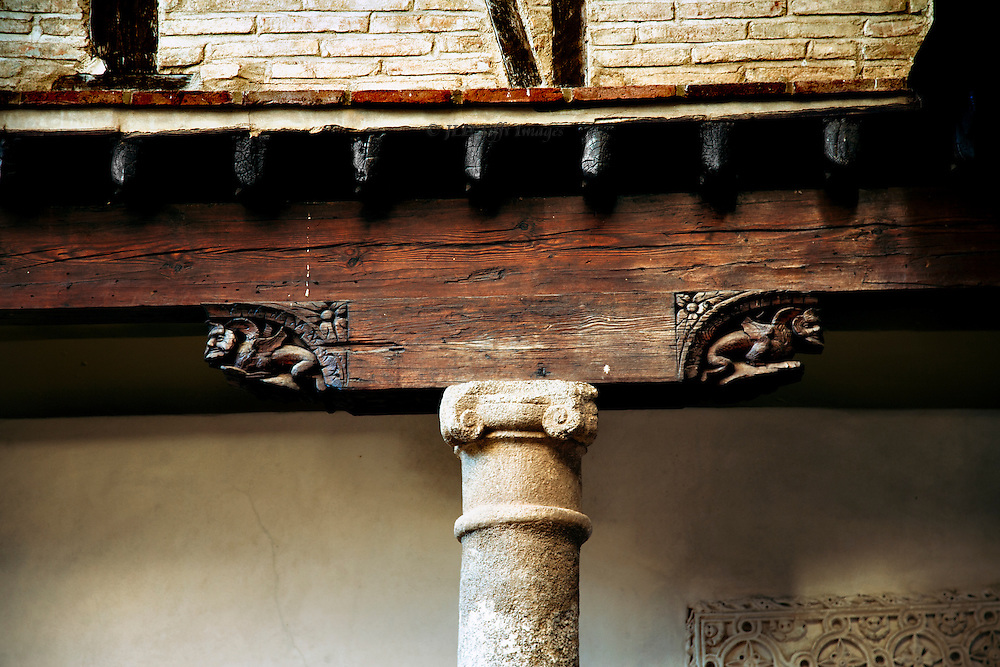 Detail of carved beam and stone proto-Ionic column capital in the courtyard of El Greco's house, Toledo, Spain.