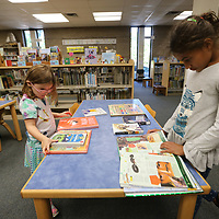 Ester Walker, 5, and her sister, Natalie, 10, look through a few books before they check them at the Lee County Library Thursday morning.