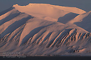 Snow-mantled fjord mountains glow in midnight sun at Austfjorden on Spitsbergen island in the Svalbard archipelago, Norway.