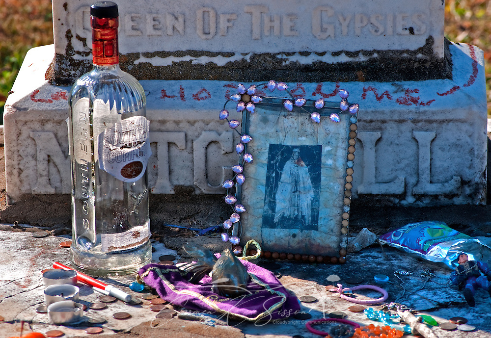 A bottle of Southern Comfort, along with candles, a fish figurine, and other items, sits on the grave of gypsy queen Kelly Mitchell at Rose Hill Cemetery in Meridian, Mississippi. Mitchell was a member of the Gypsy Royal Family, many of whom are buried nearby. Tourists and visitors often leave gifts of fruit, trinkets, and liquor on the family's graves. (Photo by Carmen K. Sisson/Cloudybright)