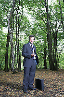 Portrait of business man in forest holding mobile phone smiling