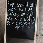 Blackboard sign in front of Hair salon with quote from Marilyn Monroe.