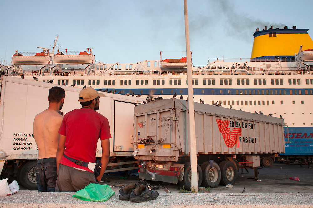 Refugees staring at the ferry to Athens in the morning light. <br /> The port of Mytilene where many refugees stay while they apply for a permit to stay in Greece or while they are waiting to board the ferry to Athens.
