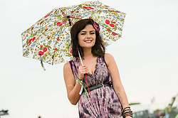© Licensed to London News Pictures. 12/06/2015. Isle of Wight, UK.  A pretty female festival goers in a summer dress and flowers shelters from the light rain with with a pretty umbrella at Isle of Wight Festival 2015 on the morning of Friday Day 2.  Yesterday the weather was hot and Sunny.  Today rain is forecast.  This years festival include headline artists the Prodigy, Blur and Fleetwood Mac.  Photo credit : Richard Isaac/LNP
