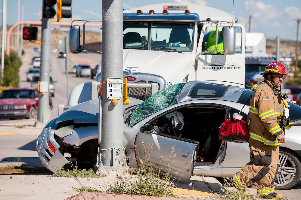 091613       Brian Leddy<br /> A Gallup firefighter walks away from the scene of an accident on Munoz Boulevard and Aztec Avenue involving  gravel truck and a passenger car.