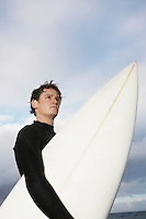 Man holding surfboard on beach side view low angle view