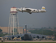 "The ""Miss Mitchell"" B-25J Mitchell bomber from the St.Paul, Minnesota Wing of the Commemorative Air Force (CAF) takes off from Kelly Field and pass by the C-5 Galaxy aircraft of the 433rd Airlift Wing on April 20, 2007. Three North American B-25 Mitchell bombers of the CAF were viewed by military families at Kelly Field, Lackland Air Force Base, TX on April 20, 2007. After the viewing, the three bombers made a 3-ship formation flyby of the Basic Military Training airmen graduation ceremonies. the aircraft were at Lackland Air Force Base to commemorate the 65th anniversary of the Doolittle air raid of Tokyo, Japan, the surviving airmen were present for a reunion during the week. (Photo copyright 2007 Lance Cheung).."