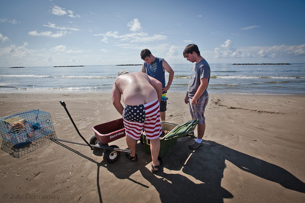A man with American flag bathing trunks, sorts through his catch of crabs letting go the  egg carrying females as required by law. His catch is smaller then what he is used to. Many fishermen report smaller catches since the BP oil spill.
