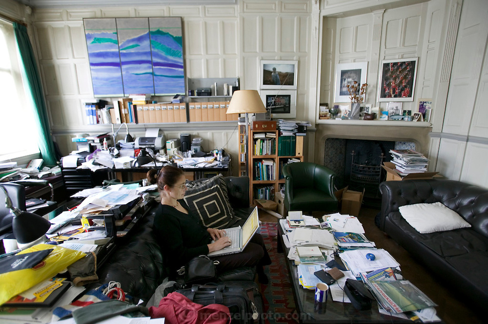 Faith D'Aluisio checking email on her computer in the cluttered home office of Philip Achache on Tite St. in London, UK..