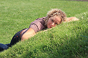 Happy woman lying on the lawn alone