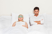 Portrait of displeased man with woman sleeping in bed