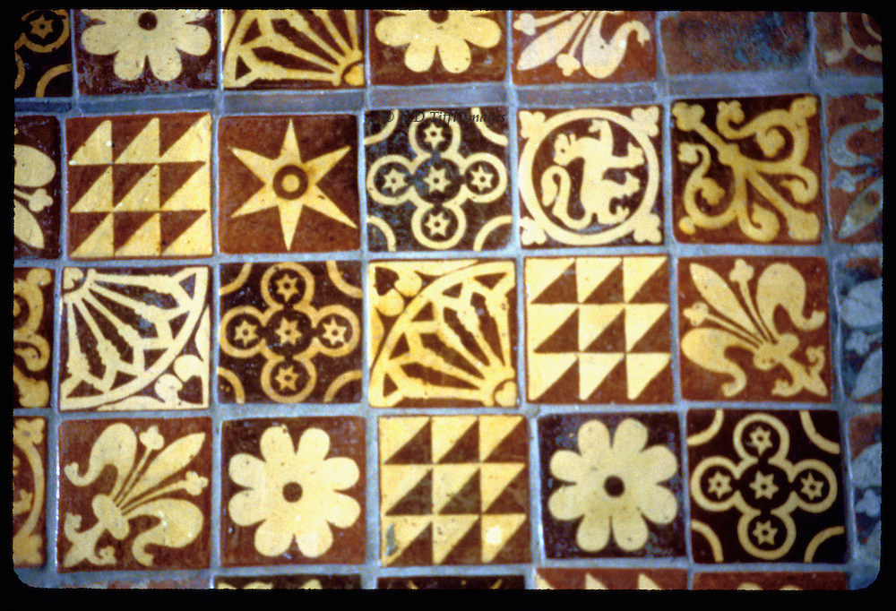 Well preserved medieval tiles in floor of Winchester Cathedral, in front of the altar.  Pattern of equal squares, each filled with a decorative motif, many different, some the same.