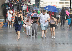 © Licensed to London News Pictures. 27/07/2018. London, UK. People get caught in a sudden downpour near Parliament as heavy rain ends the long dry spell. Photo credit: Peter Macdiarmid/LNP