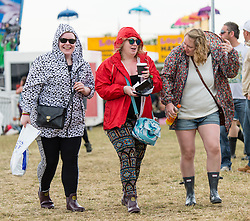 © Licensed to London News Pictures. 12/06/2015. Isle of Wight, UK.   Festival goers shelter from the light rain with anoraks and umbrellas at Isle of Wight Festival 2015 on the morning of Friday Day 2.  Yesterday the weather was hot and Sunny.  Today rain is forecast.  This years festival include headline artists the Prodigy, Blur and Fleetwood Mac.  Photo credit : Richard Isaac/LNP
