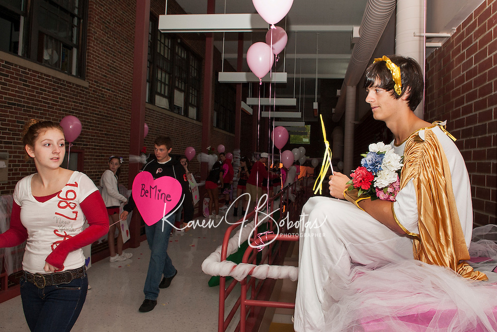 "Sophomore's Emilie Maddock, Travis Ryan and Andrew Emanuel as Cupid present their ""Valentines Day"" themed hallway for Laconia High School Homecoming festivities on Friday evening.  (Karen Bobotas/for the Laconia Daily Sun)"