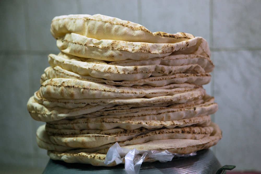 Syrian flatbread piled high on a scale at a bread factory in the early morning, Aleppo