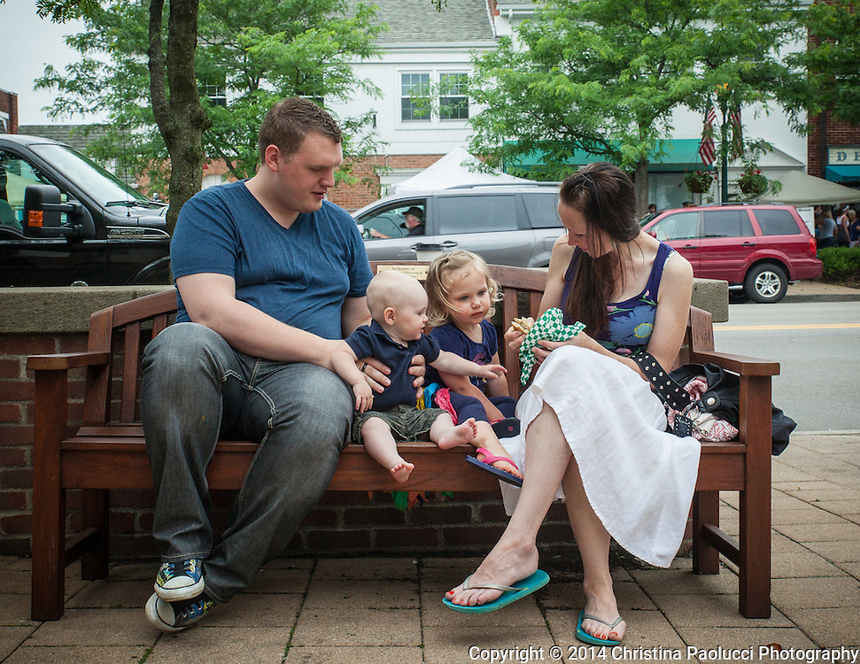 A family takes a break on a bench at the Worthington Farmer's Market Saturday June 21, 2014. (Christina Paolucci, photographer).