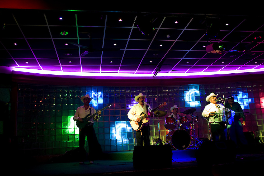 "A group of Norteno musicians play music at a night club in downtown Culiacan.  Norteno music is famous for its ""corridos"", or ballads.  Many musicians compose corridos about drug lords that become part of popular culture."