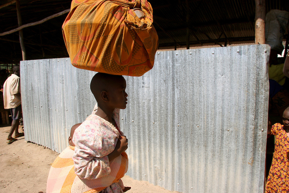 Young refugee woman and her baby carrying all her belongings in a transit camp near Makamba south of Burundi. @ Martine Perret. 14 July 2005