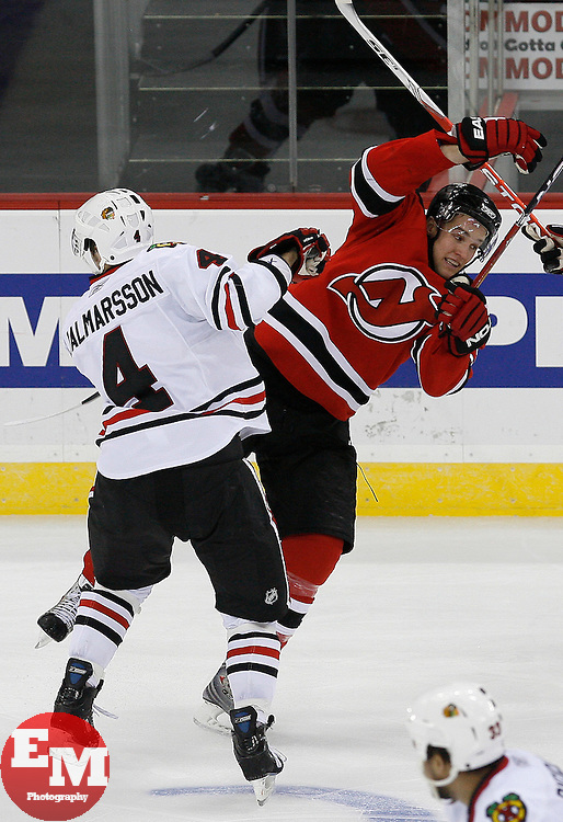 Mar 17, 2009; Newark, NJ, USA; Chicago Blackhawks defenseman Niklas Hjalmarsson (4) hits New Jersey Devils left wing Zach Parise (9) during the third period at the Prudential Center. The Devils defeated the Blackhawks 3-2 and New Jersey Devils goalie Martin Brodeur (30) became the all-time winningest goalie in NHL history with his 552 win.