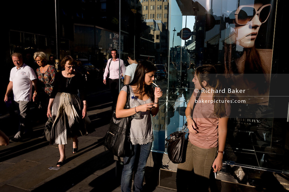 Two women smokers stand beneath a healthy poster girl for Burberry sunglasses they call Eyewear, in a sunlit London street. Burberry Group plc is a British luxury fashion house, manufacturing clothing, fragrance, and fashion accessories.