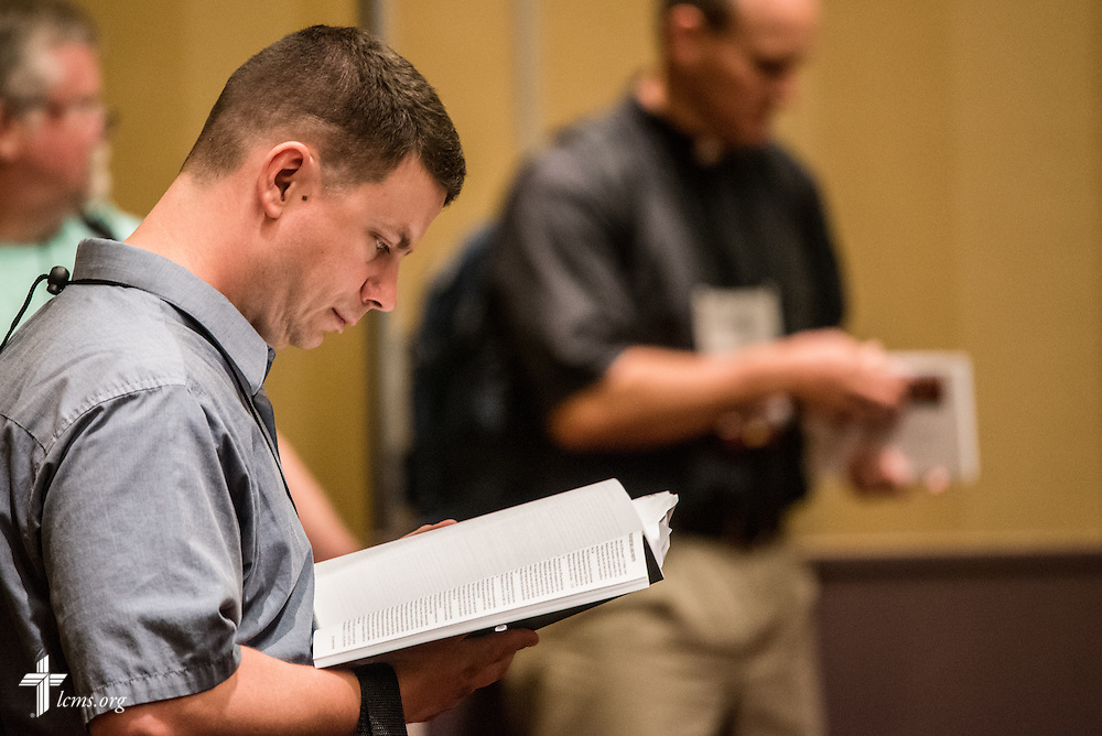 "A delegate reads the convention handbook during the open hearing of Floor Committee #12 ""Ecclesiastical Supervision and Dispute Resolution"" at the 66th Regular Convention of The Lutheran Church–Missouri Synod on Saturday, July 9, 2016, in Milwaukee. LCMS/Frank Kohn"