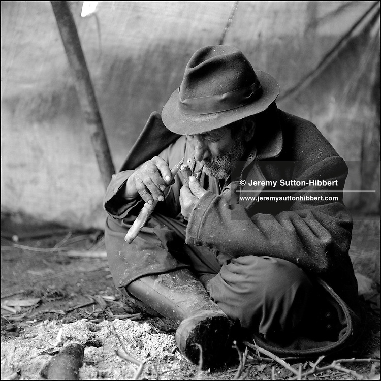 Roma elder lights a pipe of tobacco with an ember from the fire in his family tent, in the Kalderash Roma camp of Sintesti, near Bucharest. August 1994