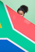 Portrait of young African American woman with South African flag against green background