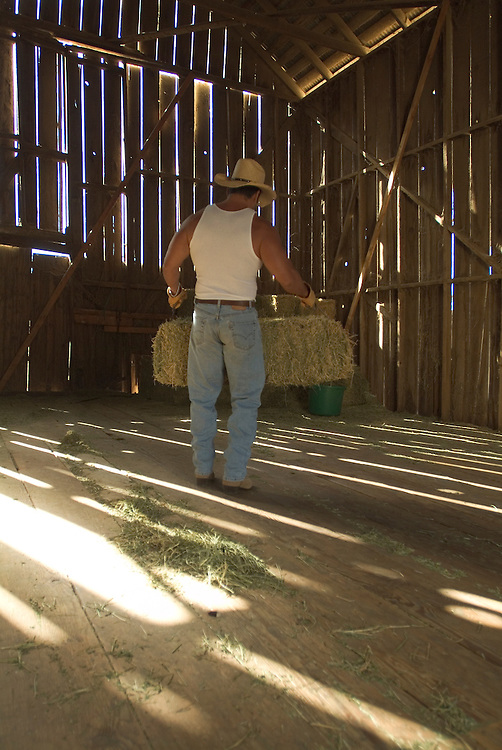 Lifestyle image of rancher hauling a hay bale in San Diego, CA.
