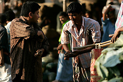 BANGLADESH DHAKA KAWRAN BAZAAR 27FEB05 - A beggar on crutches receives alms from a customer at Kawran Bazaar vegetable market. The Bazaar has been in the Tejgaon area for at least 30 years and is one of the largest markets in Dhaka city...jre/Photo by Jiri Rezac ..© Jiri Rezac 2005..Contact: +44 (0) 7050 110 417.Mobile:  +44 (0) 7801 337 683.Office:  +44 (0) 20 8968 9635..Email:   jiri@jirirezac.com.Web:    www.jirirezac.com..© All images Jiri Rezac 2005- All rights reserved.
