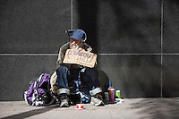 Homeless person sitting with a placard on sidewalk
