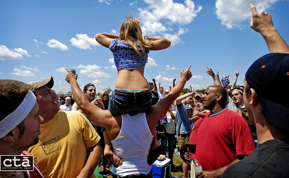 To the raucous cheers of those surrounding her, a young woman bares herself to the crowded Pimlico Race Course infield. The infield during Preakness Day is a world unto itself, separated by fences — and police — from the other  fans attending the second jewel in the Triple Crown.