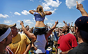 To the raucous cheers of those surrounding her, a young woman bares herself to the crowded Pinlico Race Course infield. The infield during Preakness Day is a world unto itself, separated by fences — and police — from the other  fans attending the second jewel in the Triple Crown.
