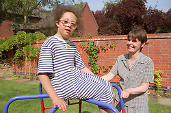 Mother supervising girl with downs syndrome playing on climbing frame in back garden,
