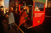 A lady passenger leaps on to the rear board of a red London Routemaster bus on a 1990s street, on 18th February 1992, in London, England. (Photo by Richard Baker / In Pictures via Getty Images)