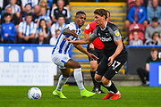 Juninho Bacuna of Huddersfield Town (7) and George Evans of Derby County (17) in action during the EFL Sky Bet Championship match between Huddersfield Town and Derby County at the John Smiths Stadium, Huddersfield, England on 5 August 2019.