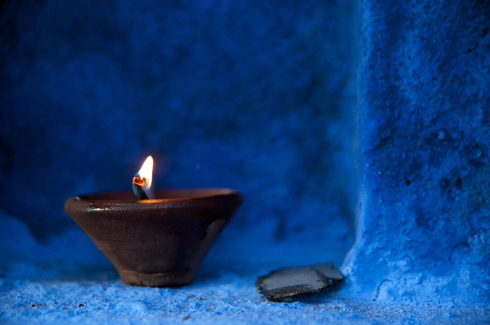 Johpur is known as &quot;The Blue City&quot; due to the Brahman neighborhoods being painted in blue.  The blue is an historic color for Brahman homes that most of the city adopted.  It is said to keep the mosquitoes at bay and the temperatures cooler.<br /> <br /> This is a candle in an earthen vessel made of clay that adorned a home during Diwali, The Festival of Lights.