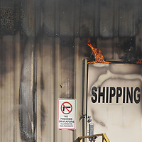 Flames begin to creep out from around service doors near the loading docks as fire engulfs most of the American Furniture plant in Ecru Friday.