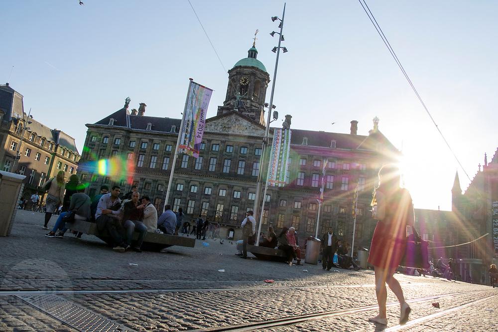 In Amsterdam steekt een vrouw in een korte rode jurk de Dam bij het paleis over.<br /> <br /> In Amsterdam a woman in a short red dress is crossing the Dam square.