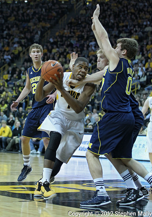 January 14, 2011: Iowa Hawkeyes forward Melsahn Basabe (1) drives around Michigan Wolverines forward Blake McLimans (22) and Michigan Wolverines guard Zack Novak (0) during the NCAA basketball game between the Michigan Wolverines and the Iowa Hawkeyes at Carver-Hawkeye Arena in Iowa City, Iowa on Saturday, January 14, 2011. Iowa defeated Michigan 75-59.