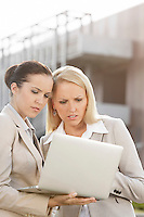 Young serious businesswomen working on laptop while standing against office building