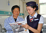 LIANSHUI, CHINA - MAY 15: (CHINA OUT) <br /> <br /> Nurses Dressed As Air Stewardesses <br /> <br /> A nurse dressed as air stewardess reads newspaper for a patient at Lianshui County Hospital of Traditional Chinese Medicine on May 15, 2014 in Lianshui county, Jiangsu Province of China. The Lianshui Huaian Hospital of Chinese Medicine has sent 12  nurses on an Eastern Airlines-style airline cabin crew training course and now requires them to wear air hostess uniforms on the wards. Bu Haijuan, the deputy chief Nurse, says the aim is to emphasise the personal service aspect of the hospital\'s care. <br /> ©Exclusivepix