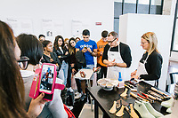 """ROME, ITALY - 15 OCTOBER 2018: Fabio (2nd from right), a shoemaker working for FENDI, makes a show and exaplins its process to students during the LVMH Journées Particulières exhibition at the Fendi headquarters in Rome, Italy, on October 15th 2018.<br /> <br /> The LVMH Journées Particulières is is a series of exhibitions that show the creations and history of the LVMH fashion houses. The driving theme behind the Journées Particulières is to allow the general public to discover the inner workings of the Houses which are part of the LVMH heritage.The LVMH Journées Particulières exhibition by fashion house FENDI takes place at their headquarters at the Palazzo della Civiltà Italiana, also called the """"Colosseo Quadrato"""" (Square Colosseum),  an outstanding jewel of the 20th century Roman architecture."""