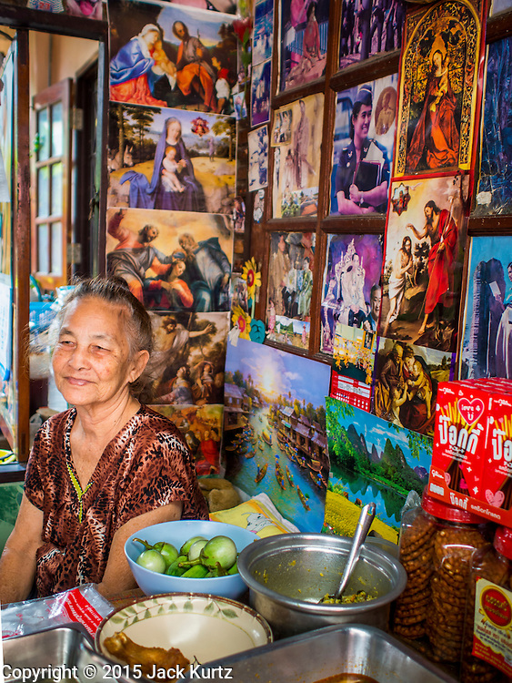 11 FEBRUARY 2015 - BANGKOK, THAILAND:  YUPIN, 77, a Catholic woman in her small snack stand near Santa Cruz Church in the Thonburi section of Bangkok. The woman is Catholic and her shop is decorated with Catholic art and pictures of the Thailand's Buddhist monarchy. The neighborhood around the church is known for the Thai adaptation of Portuguese cakes baked in the neighborhood. Several hundred Siamese (Thai) Buddhists converted to Catholicism in the 1770s. Some of the families started baking the cakes. When the Siamese Empire in Ayutthaya was sacked by the Burmese, the Portuguese and Thai Catholics fled to Thonburi, in what is now Bangkok. The Portuguese established a Catholic church near the new Siamese capital. There are still a large number of Thai Catholics living in the neighborhood around the church.           PHOTO BY JACK KURTZ