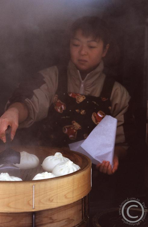 A young Japanese girl prepares Nikuman - steamed pork buns, in Sapporo, Hokkaido, Japan