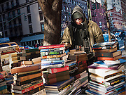 Used book stall owner smokes a cigar at Columbus Avenue at 68th Street, New York City.
