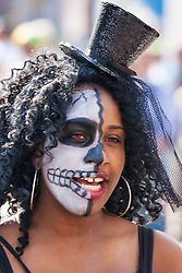 London, August 24th 2014. A woman in her startling makeup heads for the procession as revellers prepare to participate in 2014's Notting Hill Carnival in London, celebratingWest Indian and other cultures, and attracting hundreds of thousands to Europe's biggest street party.