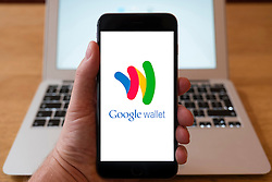 Using iPhone smartphone to display logo of Google Wallet mobile payment and  digital payment system