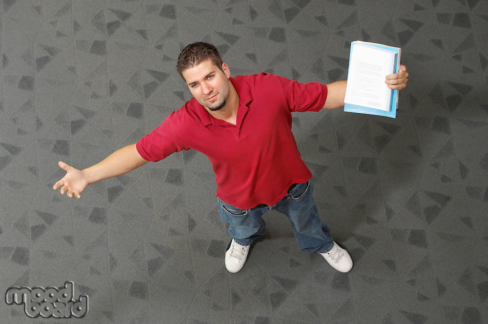 Male student with arms outstretched, indoors, portrait